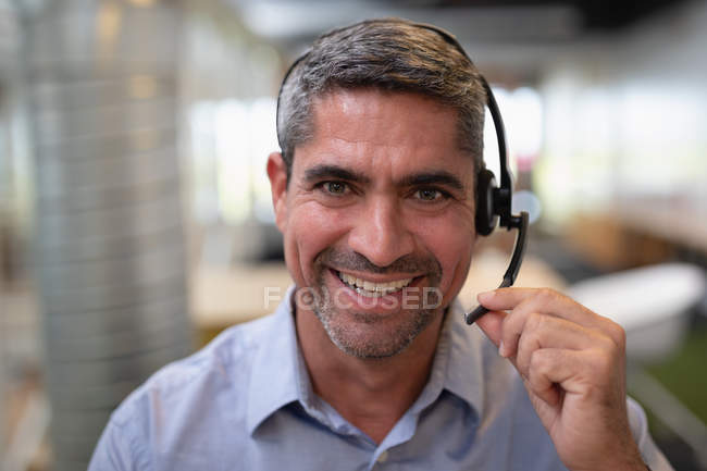 Portrait of a happy businessman smiling at the camera while holding a headphone in office — Stock Photo