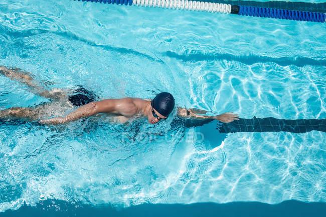 Erhöhte Ansicht des jungen kaukasischen männliche Schwimmer Schwimmen Freistil im Außenpool in der Sonne — Stockfoto