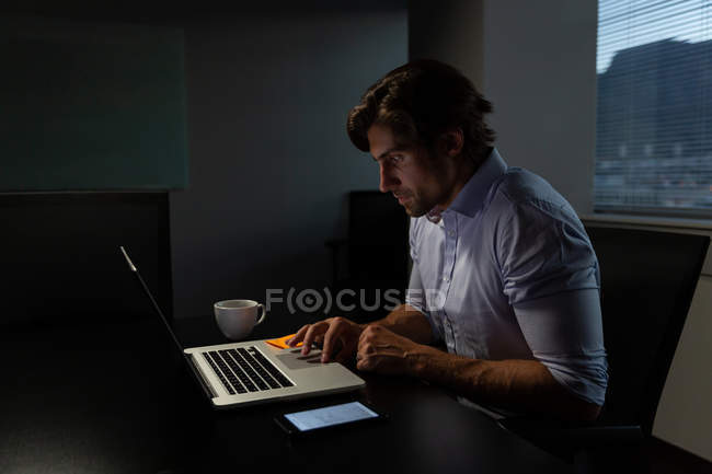 Side view of young male executive sitting at table and working on laptop in a modern office — Stock Photo
