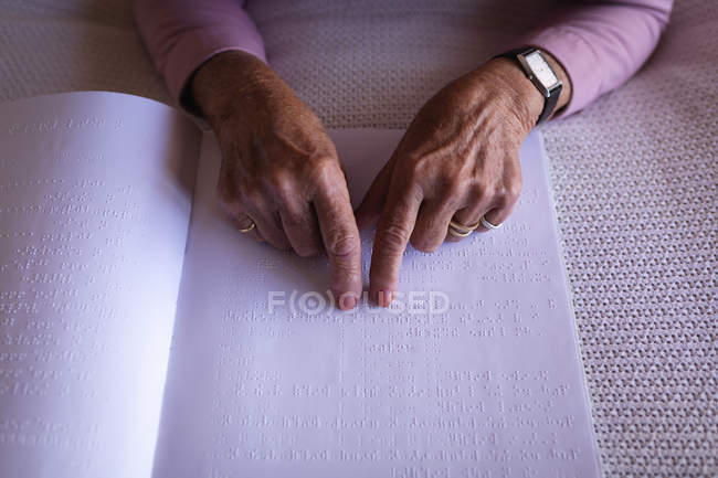 Close-up of a blind active senior woman reading a braille book with her fingers on the bed in bedroom at home — Stock Photo