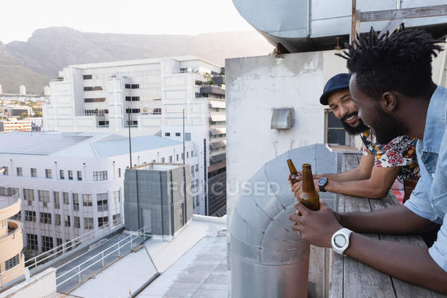 Side view of Male multi ethnic friends interacting with each other while having beer in hands at balcony — Stock Photo