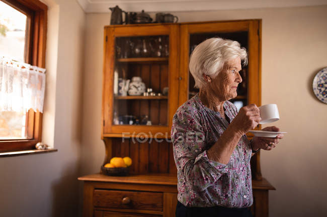 Side view of a thoughtful active senior woman drinking her coffee while standing in the kitchen at home — Stock Photo
