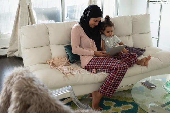 Вид спереди матери со смешанным расовым происхождением в хиджабе и дочери, сидящей и использующей цифровой планшет в гостиной дома — стоковое фото