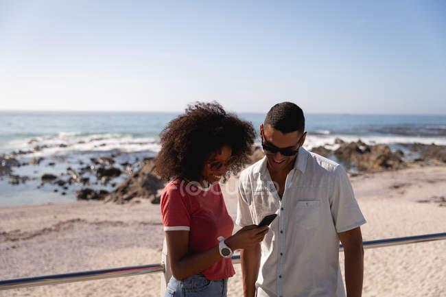 Vista frontal do casal afro-americano usando telefone celular e sorrindo na praia em um dia ensolarado — Fotografia de Stock