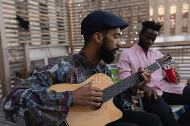 Side view of African american Man playing guitar while other friend having cold drink in balcony at home — Stock Photo
