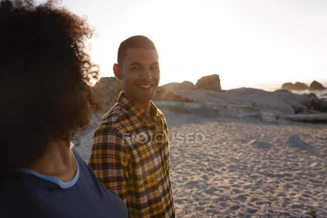 Vista laterale della coppia afro-americana che sorride e si guarda vicino al mare. Sono in piedi su zibellino al tramonto — Foto stock