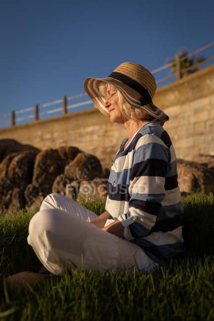Seitenansicht einer aktiven senior Frau Durchführung Yoga auf dem Rasen vor der Sonne — Stockfoto