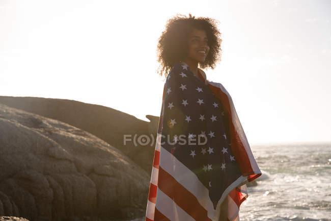 Vue de côté de la femme afro-américaine debout et enveloppé drapeau américain près du côté de la mer — Photo de stock