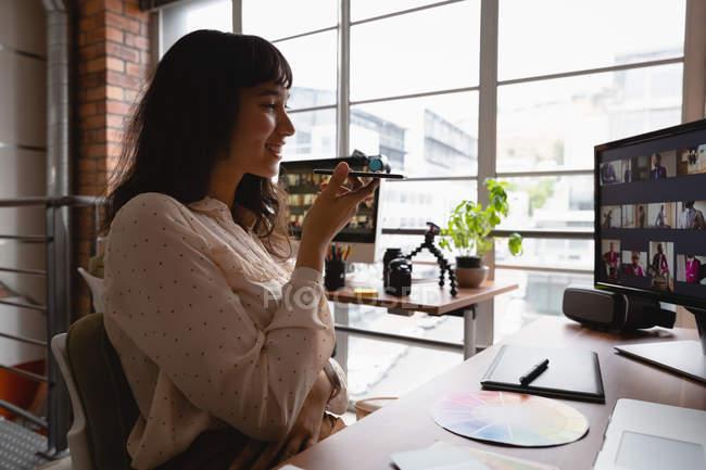 Vista lateral de la mujer de negocios hablando y utilizando el teléfono inteligente en la oficina - foto de stock
