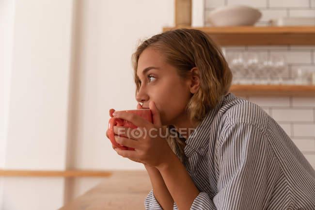 Vista laterale della donna premurosa che prende una tazza di tè mentre si trova in cucina — Foto stock