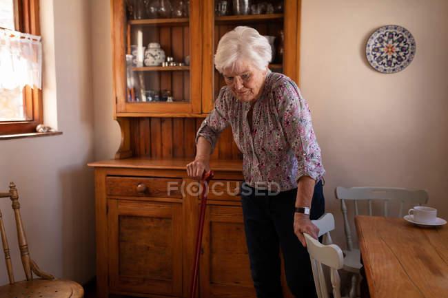 Vorderansicht eines aktiven senior Frau zu Fuß mit einem Stock in der Küche zu Hause — Stockfoto