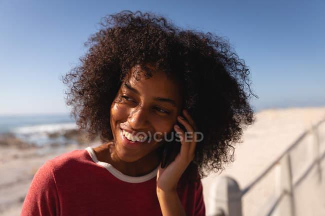 Gros plan de femme afro-américaine parlant sur son téléphone portable tout en souriant à la plage — Photo de stock