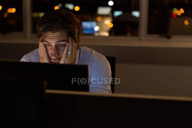 Vista frontal da cansado executivo masculino jovem com as mãos no rosto, trabalhando na mesa em um escritório moderno. Ele está trabalhando até tarde — Fotografia de Stock