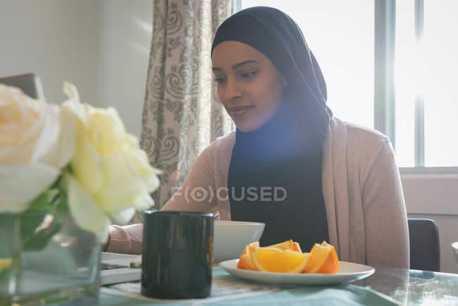 Niedrigen Winkel Ansicht der jungen gemischt Rennen schöne Frau tragen Hijab arbeiten am Laptop zu Hause — Stockfoto