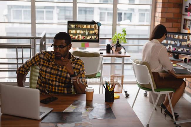 Vue de face de divers hommes d'affaires travaillant sur ordinateur portable dans le bureau — Photo de stock