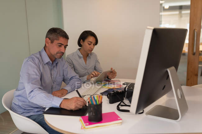 Side view of multi ethnic graphic designers working together in the office — Stock Photo