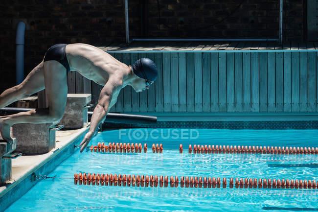 Vue latérale du jeune nageur masculin caucasien sautant dans l'eau d'une piscine extérieure le jour ensoleillé — Photo de stock