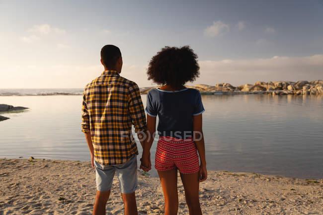 Вид сзади на афро-американскую пару, стоящую на пляже на песке. Они смотрят на море. — стоковое фото