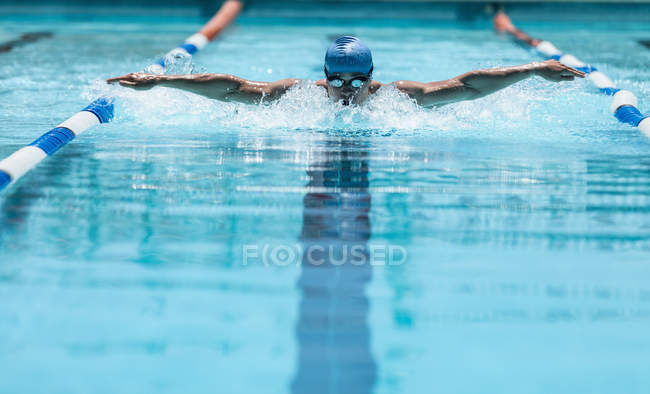 Front view of young Caucasian male swimmer swimming butterfly stroke in outdoor swimming pool in the sunshine — Stock Photo