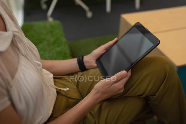 Vista de ángulo alto de una mujer de negocios sosteniendo una tableta digital mientras está sentada en la oficina - foto de stock