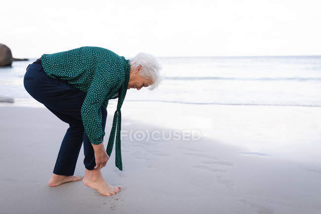 Side view of an active senior woman rolling up her pant sleeves while standing next to the waterside on the beach — Stock Photo