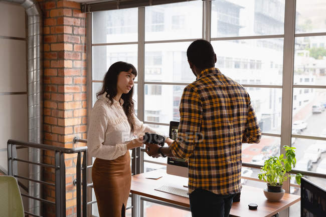 Front view of diverse business people discussing with each other in office. African american holding camera — Stock Photo