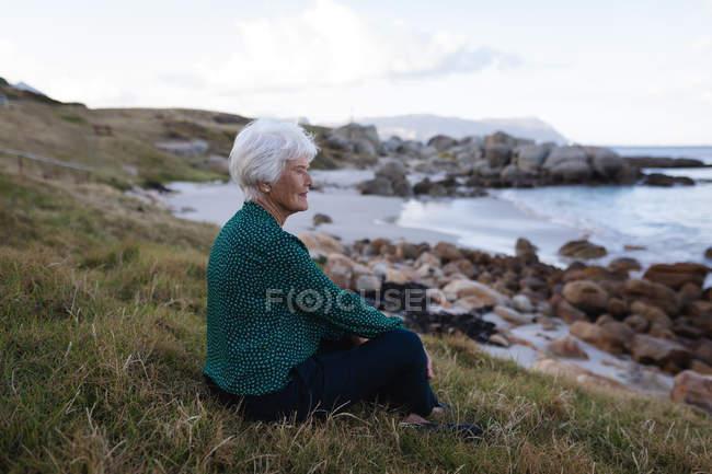 Вдумчивый активные старший женщина, сидящая на траве на пляже и глядя на море, вид сбоку — стоковое фото