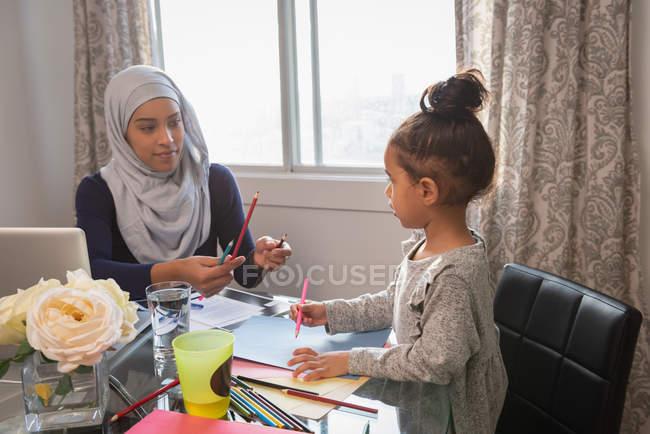Vorderansicht der Mischlinge Mutter tragen Hijab und Tochter sprechen miteinander zu Hause an einem Tisch — Stockfoto