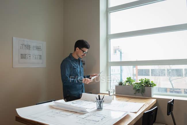 Vue latérale de l'homme d'affaires permanent et à la recherche de plan directeur au bureau salle de réunion — Photo de stock
