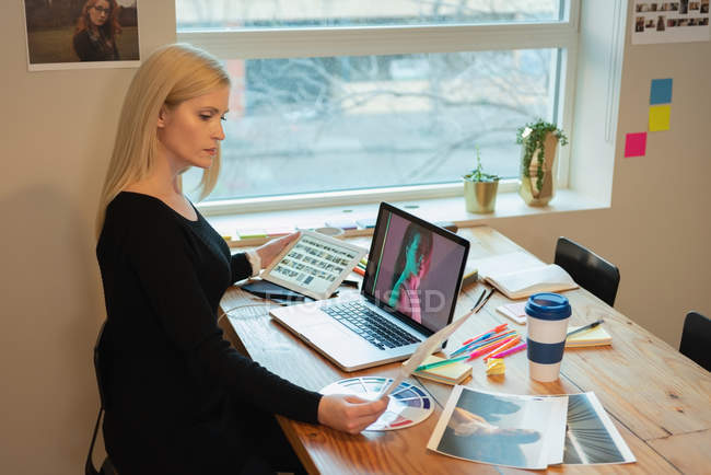 Вид сбоку вдумчивый кавказской бизнесвумен, глядя через ноутбук и проведение таблетка в руке в офисе — стоковое фото