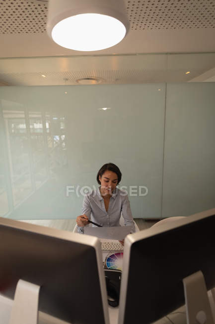 Front view of an Asian graphic designer looking at sketches in her office — Stock Photo
