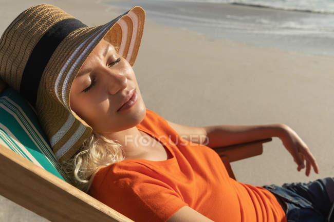 Крупный план расслабленной молодой женщины, отдыхающей на шезлонге на пляже в солнечный день. Она носит шляпу. — стоковое фото