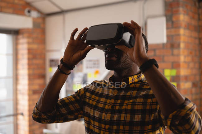 Front view of african-american businessman using virtual reality headset in office — Stock Photo