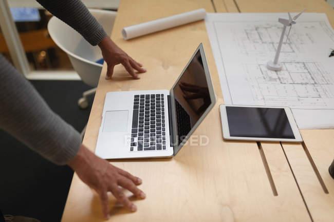 Parte centrale di un uomo d'affari appoggiato alla scrivania e che guarda il suo portatile — Foto stock