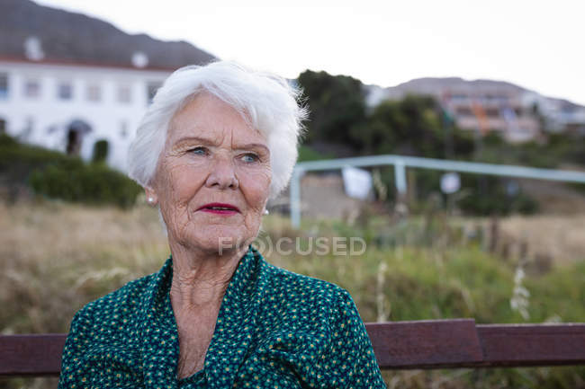 Front view of a thoughtful active senior woman sitting on wooden bench at sea — Stock Photo