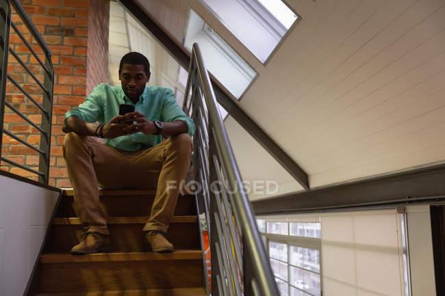 Vue de face d'homme d'affaires afro-américaines à l'aide de téléphone portable à l'escalier au bureau — Photo de stock