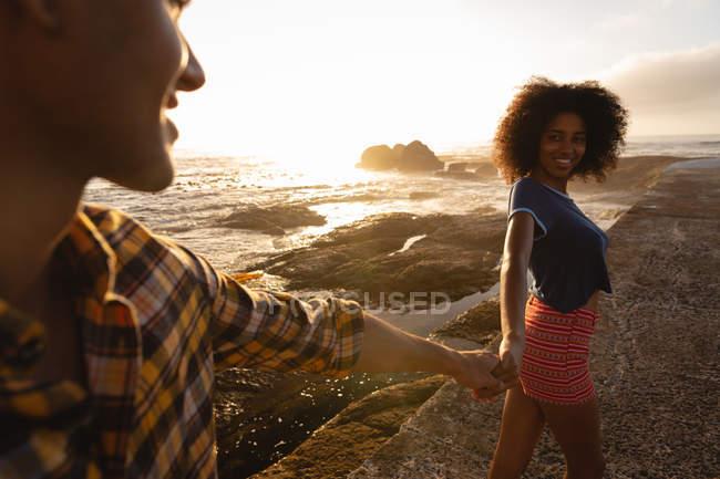 Vue de face d'Afro-Américains couple main dans la main, debout sur la roche près de bord de mer. Ils sont souriants et regarder les uns des autres — Photo de stock