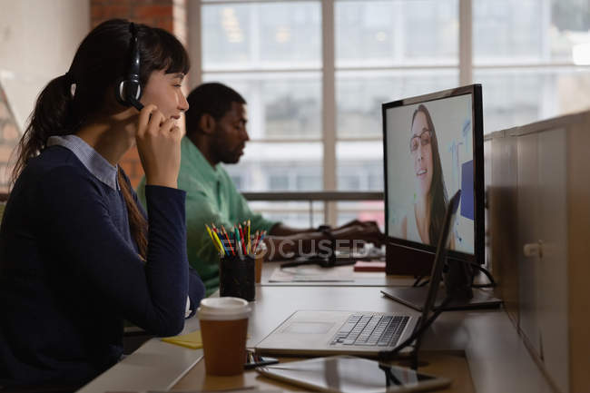 Side view of businesswoman making video call to business partner in office at desk — Stock Photo