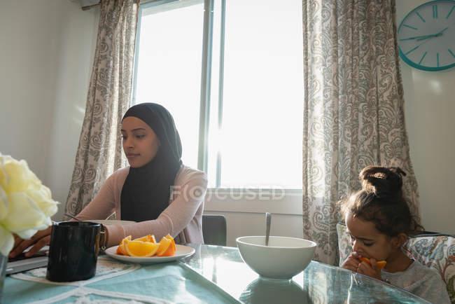 Niedrigen Winkel Ansicht der Mischlinge Mutter tragen Hijab mit Laptop während Tochter essen Obst zu Hause — Stockfoto