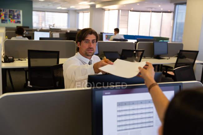 Vista frontale di bei dirigenti maschi che danno un pezzo di carta alla collega caucasica alla scrivania in un ufficio moderno — Foto stock