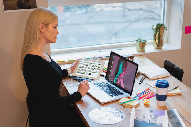 Вид сбоку вдумчивый кавказской бизнесвумен, глядя через ноутбук и проведение таблетка в офисе — стоковое фото