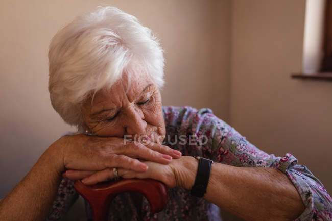 Front view of an active senior woman sleeping and leaning on a cane in the kitchen at home — Stock Photo