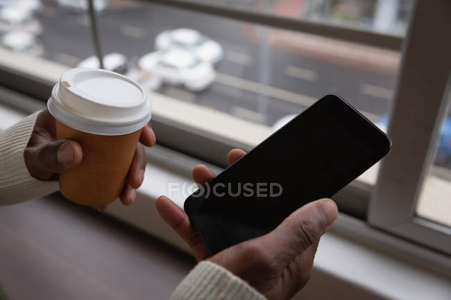Close up of businessman using mobile phone and coffee cup in each hands in office canteen — Stock Photo