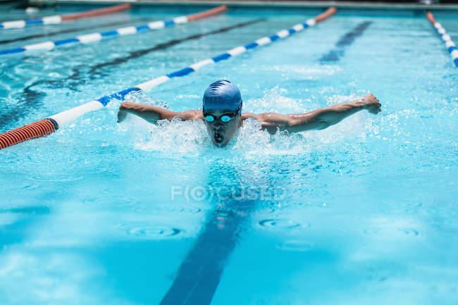 Вид спереди на молодого кавказского пловца, плавающего бабочкой в бассейне под солнцем — стоковое фото