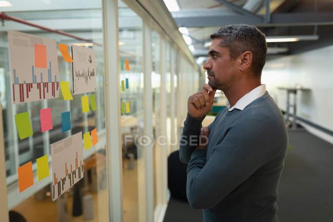 Вид збоку вдумливі бізнесмена, дивлячись на наліпок виправлено на стіні в офісі — стокове фото