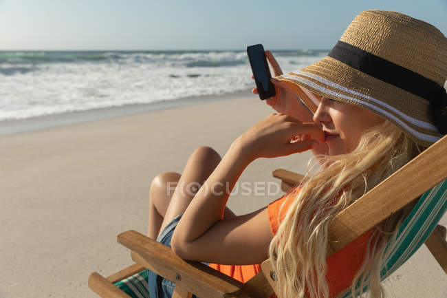 Вид збоку жінки розслабляючий на шезлонгу на пляжі у сонячний день. Вона сидить і використовуючи свій мобільний телефон — стокове фото