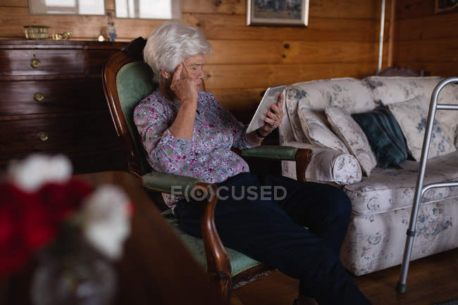 Side view of an active senior woman with her hand on her temple using a digital tablet while sitting on an armchair at home — Stock Photo