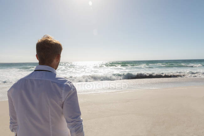 Rear view of relaxed man standing at beach on a sunny day. He is walking — Stock Photo