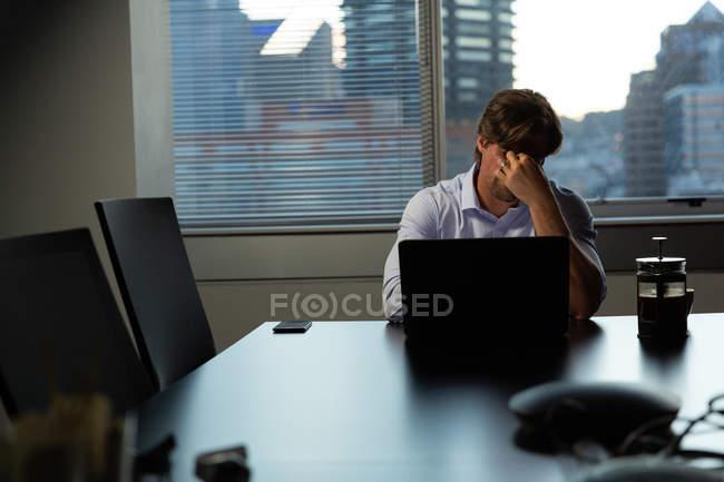 Vista frontal do cansado jovem masculina executiva esfregando os olhos enquanto estiver trabalhando no laptop na mesa em um escritório moderno — Fotografia de Stock