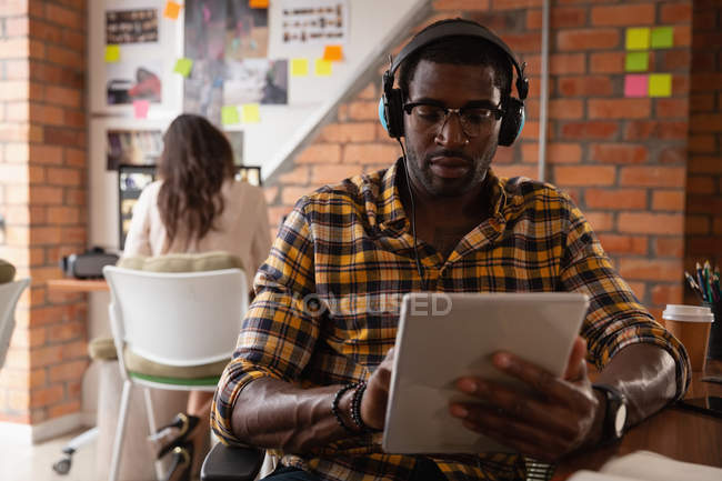 Front view of African american businessman using digital tablet with head phones in office while a caucasian woman working behind him — Stock Photo